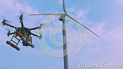 Il fuco decolla dalle mani di una ragazza vicino ad un generatore eolico, movimento lento stock footage