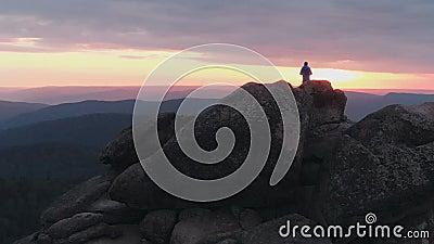 Il fuco ha sparato dell'uomo solo che sta sopra una montagna e che gode del tramonto video d archivio