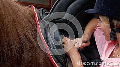 Il giovane amazzone in casco di guida fissa le cinghie sulla sella, primo piano 4K video 4K video d archivio