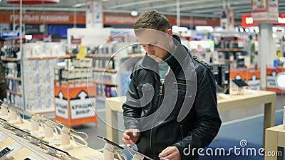 Il giovane in bomber nero sta scegliendo un nuovo telefono cellulare in un negozio, controllante come funziona stock footage