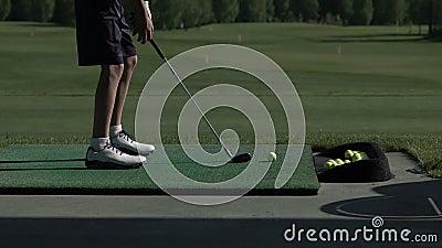 Il giovane giocatore di golf pratica la sua oscillazione del golf sulla gamma di azionamento, vista dal lato video d archivio