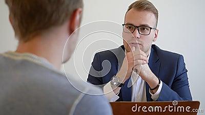 Il giovane impiegato del responsabile con il cliente si siede alla tavola dello scrittorio Una conversazione di due giovani L'uom stock footage