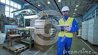 Il lavoratore maschio cammina in una funzione, scrivente su una compressa, attrezzatura della fabbrica stock footage