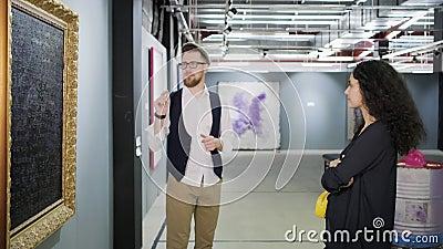 Il lavoratore maschio del museo sta parlando del materiale illustrativo dell'artista moderno nella mostra stock footage