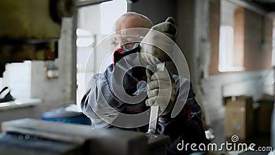 Il lavoratore maschio invecchiato sta regolando la macchina in un'officina della fabbrica, chiave girante e sta utilizzando il ma archivi video