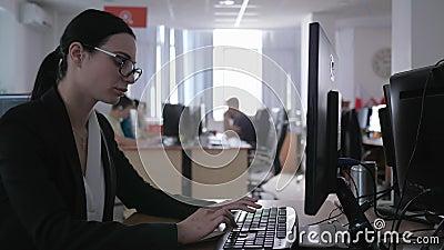 Il lavoro d'ufficio duro, ragazza frustrata di affari con i vetri utilizza il computer e fa le note video d archivio