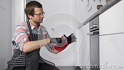 Il marito cucina i biscotti in forno per tutta la famiglia È importante regolare la modalità per una corretta cottura stock footage