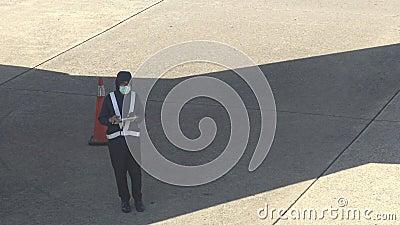 il meccanico asiatico di manutenzione di aerei 4K ispeziona la fusoliera piana in aeroporto video d archivio
