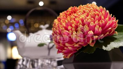 Il moto di tè caldo ed il fiore su moto della sfuocatura e della tavola della gente godono del pasto dentro il ristorante video d archivio