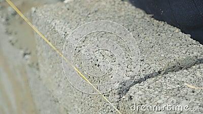 Il muratore costruisce il muro di mattoni, vista del primo piano al cantiere stock footage