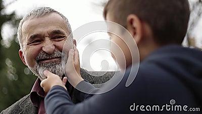 Il nipote tocca la bella barba di suo nonno stock footage