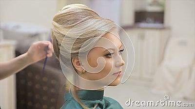 Il padrone dei capelli spruzza la vernice, fa i riccioli, la bionda, il salone di bellezza, movimento lento archivi video