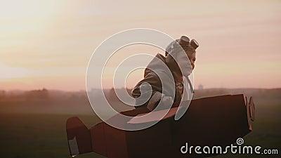Il piccolo ragazzo pilota felice comincia funzionare in aereo del cartone di divertimento sul campo di autunno del tramonto, gioc archivi video