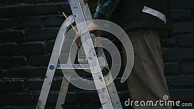 Il pittore Climbed le scale ed ha preso un barattolo con pittura nera stock footage
