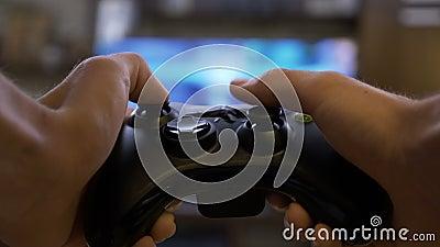 Il primo piano del giovane passa il gioco dei video giochi sulla console di gioco davanti alla TV a grande schermo - archivi video