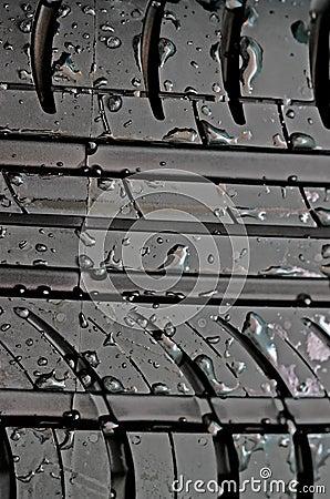 Il primo piano della gomma di automobile con con acqua cade