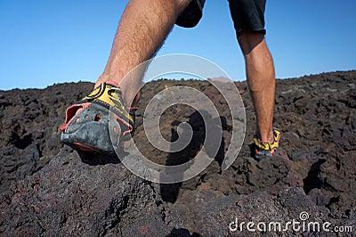 Il primo piano di uomo i piedi che camminano sul giacimento di lava