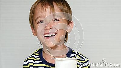 Il ragazzino ride della macchina fotografica Il bambino si siede alla tavola e mangia il yogurt Emozioni felici Alimenti per bamb stock footage