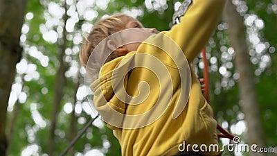 Il ragazzino in un cavo di sicurezza guida uno zipline in cime d'albero in un parco di avventura della foresta Scala sull'alta tr stock footage