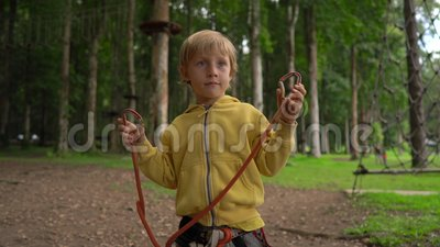 Il ragazzino in un parco di avventura della foresta mostra suo un cavo di sicurezza Centro all'aperto di divertimento con le atti stock footage