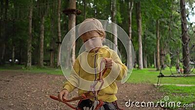 Il ragazzino in un parco di avventura della foresta mostra suo un cavo di sicurezza Centro all'aperto di divertimento con le atti video d archivio