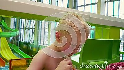 Il ragazzo mangia patatine fritte Un ragazzino con i capelli biondi mangia cibo veloce archivi video