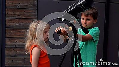 Il ragazzo mostra ad una ragazza un telescopio stock footage