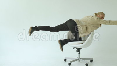 Il rallentatore dell'uomo d'affari divertente barbuto si diverte la guida sulla sedia dell'ufficio su fondo bianco stock footage