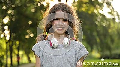 Il ritratto di piccolo studente caucasico attraente Girl With Beautiful Brown osserva con le cuffie Bambino sorridente felice archivi video
