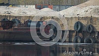 Il secchio della gru a benna dei lavandini dell'escavatore nel fiume al porto contro lo sfondo di vecchia, chiatta arrugginita e  video d archivio