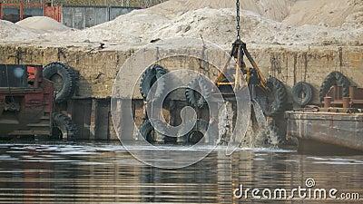 Il secchio della gru a benna dell'escavatore aumenta dal fiume con spruzza dell'acqua nel porto contro lo sfondo dell' stock footage