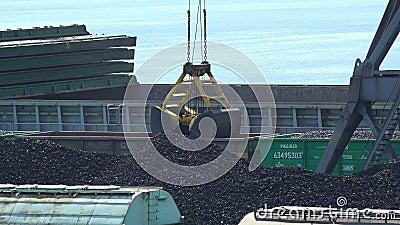 Il secchio della gru a benna scarica il carbone dai vagoni in un cargo video d archivio