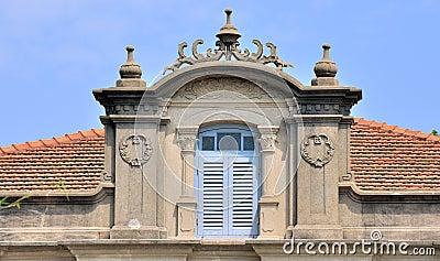 Il tetto della costruzione con squisito intaglia e finestra blu