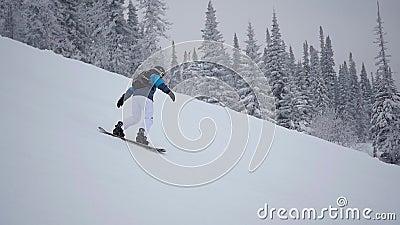 Il tipo discende dalla montagna sullo snowboard in slowmo stock footage