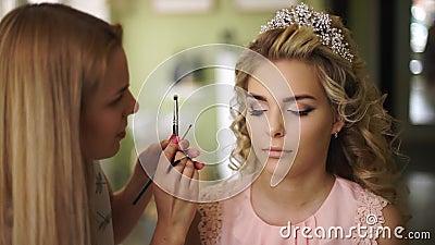 Il truccatore dipinge il fronte della sposa, in un bello salone Trucco professionale per la donna con il giovane fronte sano archivi video