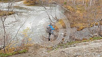 Il viaggiatore con uno zaino è sulla traccia Si avvicina alla torrente montano e con l'aiuto dei passaggi speciali dei bastoni archivi video