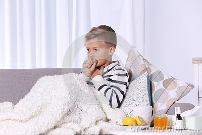 Ill boy suffering from cough on sofa Stock Photo