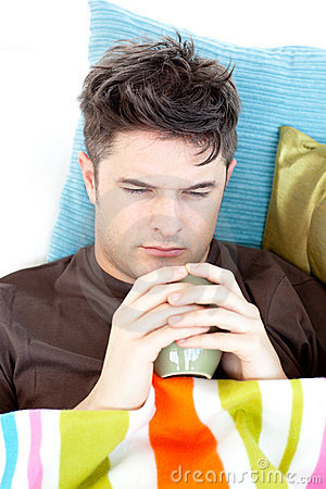 Ill depressed man holding coffee lying on the sofa