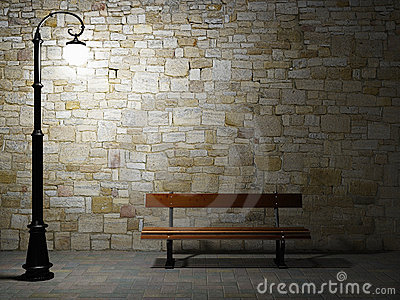 Illuminated brick wall with street light and bench