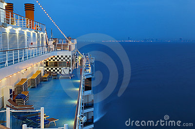 Illuminated cruise ship with people in sea