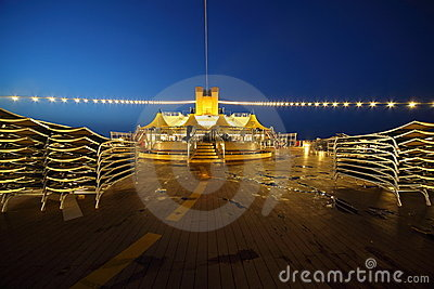 Illuminated deck of cruise ship at evening.