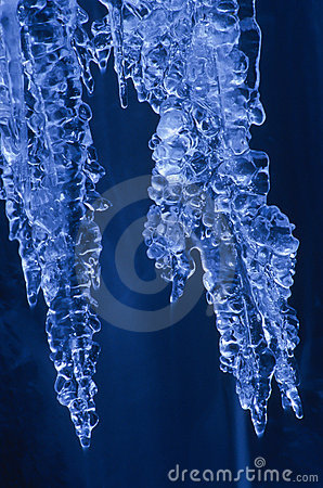Illuminated large icicles hanging by waterfall