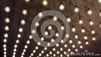 Iluminação de uma variedade de bulbos incandescentes que penduram no teto e vão ao defocus video estoque