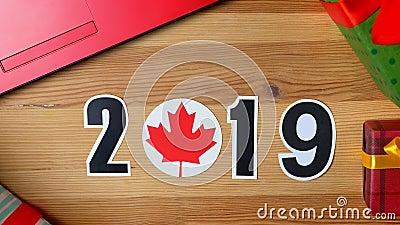 A ilustração, ano novo, a mão masculina pôs sobre a tabela sobre a bandeira canadense, bola do país, 2019 video estoque