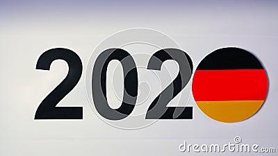 Ilustracja, nowy rok, męska ręka stawiająca dalej stół na niemiec flaga, kraj piłka, 2020 zdjęcie wideo