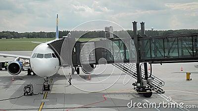 Im Flugzeug landen Leute ?berschreiten durch das jetbridge an Bord einer unerkannten Fluglinie Das Konzept von Ferien und stock footage