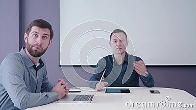 Im Konferenzzimmer mit Tablette und Laptop sitzender und höflich besprechender Geschäftsmann zwei von mittlerem Alter auf dem Sch stock video footage