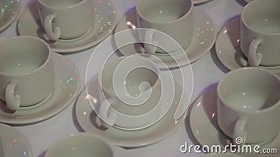 Im Restaurant auf einem Tabellenstand ordneten weiße Tassen und Untertassen Viele Cup stock video footage