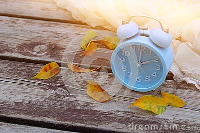 Image of autumn Time Change. Fall back concept. Dry leaves and vintage alarm Clock on wooden table outdoors at afternoon