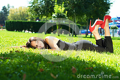 Image of a beautiful young woman lying and posing in green grass